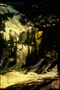 Sun slanting into a steep-sided valley between forested hills.